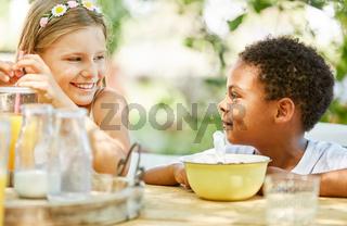 Mädchen und afrikanischer Junge beim Frühstück