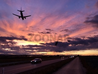A plane is approaching Stuttgart AIrport during a dramatic sunset