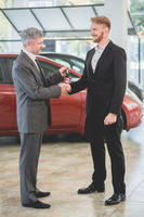 Vehicle dealer passing key from new car to a buyer.