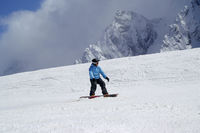 Snowboarder downhill on snowy ski slope in high mountain