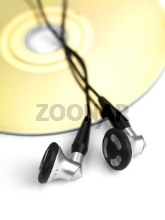 A stock of compact discs and ear phones isolated against a white background
