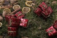 Weihnachtsdekoration mit Zimt, Nüssen, Orangenschalen und Geschenken