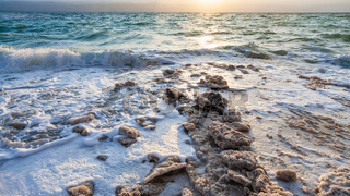 crystals of salt on shore of Dead Sea on sunset
