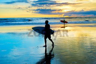 Surfers walking on the beach