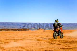 Ait Saoun, Morocco - February 22, 2016: Rare view of man in helmet riding bike in Ait Saoun desert of Morocco.