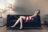 Fashion portrait of young beautiful woman laying down on sofa in dress made with usa flag