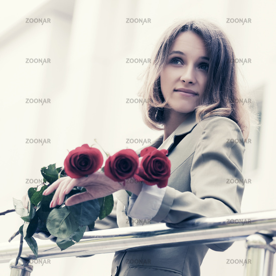 Happy young fashion woman with red roses outdoor