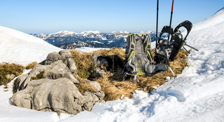 Winter hiking equipment. Backpack and snowshoes on top of mountain.