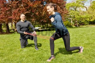 Frau bei Fitnesstraining im Park mit Gummiband