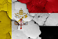 flag of Vatican and Yemen painted on cracked wall