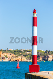 Beacon and buoy with blue water at coast
