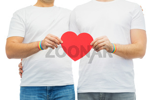 couple with gay pride rainbow wristbands and heart