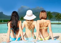 group of women in swimwear sunbathing on beach