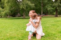 happy mother hugging baby girl at summer park