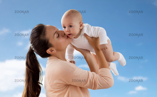 happy mother kissing little baby boy over sky