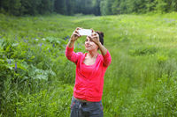 Woman making photo at mountain forest