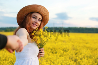 Girl in straw hat in a field of yellow flowers blossoming