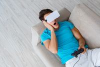 Young man wearing VR glasses relaxing on couch sofa