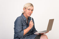 beautiful european mid aged woman working at a laptop thoughtful