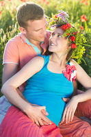 Young beautiful pregnant couple in poppy field.