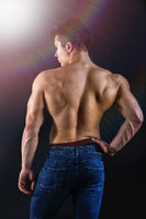 Back of young muscleman standing shirtless on black background