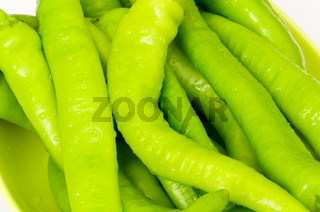 Many green hot peppers arranged at the market