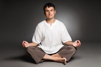 Peaceful man meditating isolated over dark