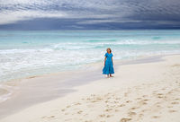 The woman in a long blue dress goes on the sea coast Cayo Largo's island