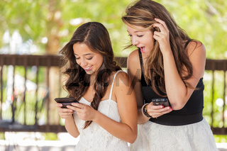 Two Expressive Mixed Race Girlfriends Using Their Smart Cell Phones Outdoors