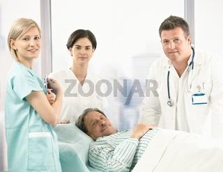 Portrait of senior patient with hospital crew