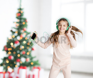 girl with smartphone and headphones at christmas