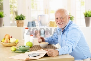 Cheerful senior man having breakfast