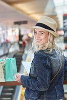 Junge Frau im Einkaufszentrum mit Kreditkarte