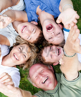 Multi-generation family lying in circle and laughing at camera with raised arms
