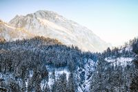 Sunrise in snowy winter mountains and woodland. Hintersteiner Tal, Allgau, Bavaria, Germany.