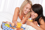 Two girlfrinds having breakfast in white bed