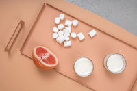 Grapefruit, marshmallows and glasses with milk