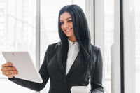 Successful confident young business woman working with tablet in an office setting