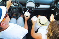 Happy couple driving in car with coffee