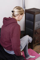 Frau sitzt am Ofen