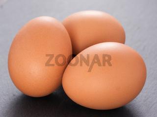three eggs on slate background