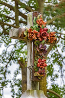 Old stone crucifix adorned with flowers