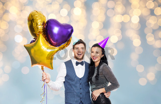 couple with party caps and balloons over lights