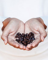 Closeup coffee bean in women hands concept for good morning and giving refreshing with shallow depth of field.