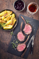 Barbecue Rack of Venison with Roast Potatoes and Cranberries as top view on a black slate