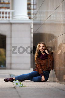 Happy young fashion woman in leather jacket sitting on city street