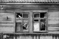black and white photo old wooden village abandoned house with broken glass in windows, Russia.