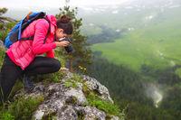 Woman with camera making photo on mountain peak