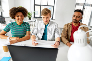 creative team looking at laptop papers at office