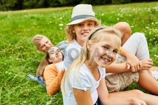 Blondes Mädchen und Familie auf einer Wiese